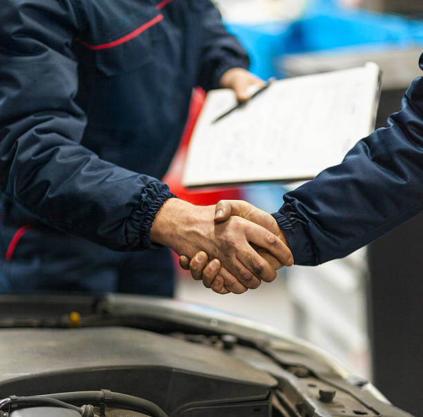 Auto mechanics shaking hands.